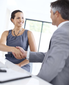 Smiling young business woman shaking hands with a male executive while sitting at a desk